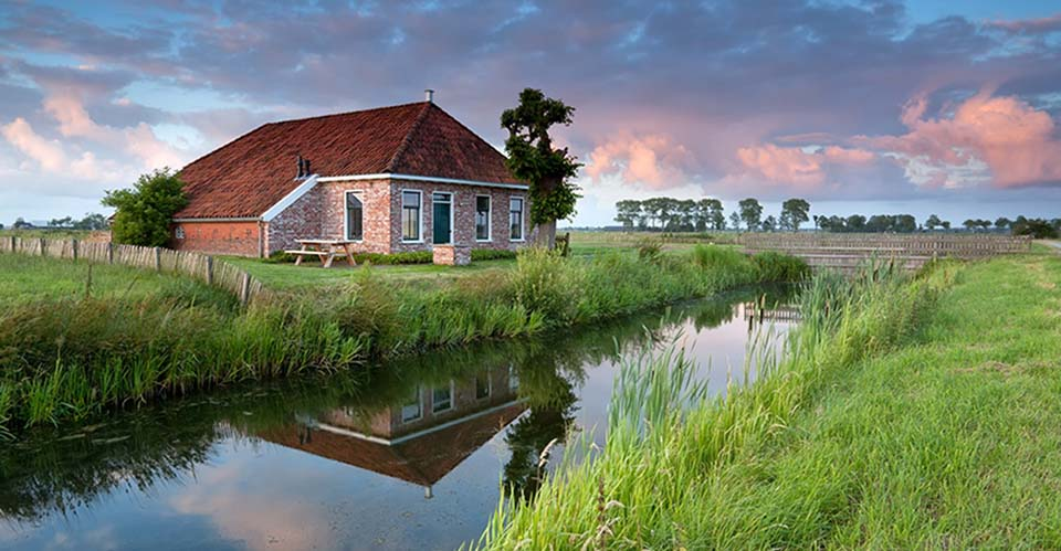 beautiful cozy farmland by river at sunset